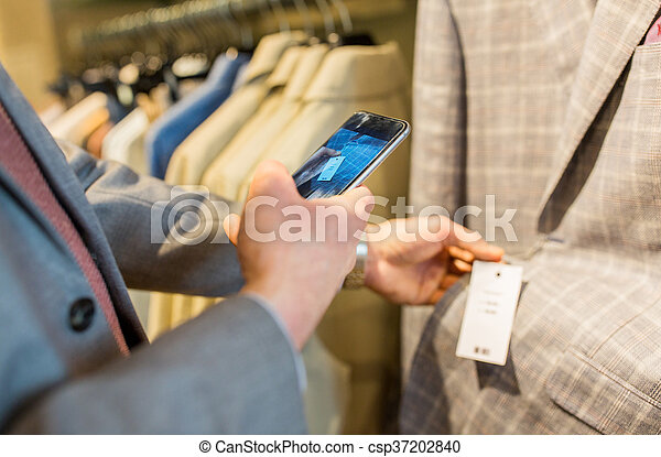 close up of man with smartphone at clothing store - csp37202840