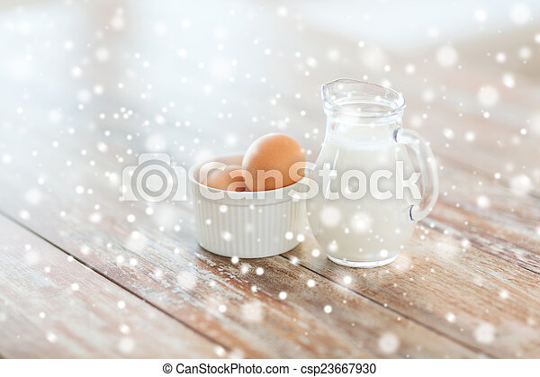 close up of milk jugful and eggs in bowl - csp23667930