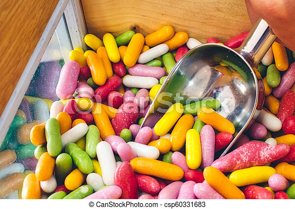 Close-up of multi-colored candy sticks / sweets with a hand filling a scoop from a wooden box - csp60331683