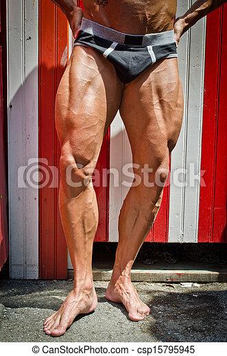 Close-up of muscular legs outdoors. Close-up of man muscular legs ...