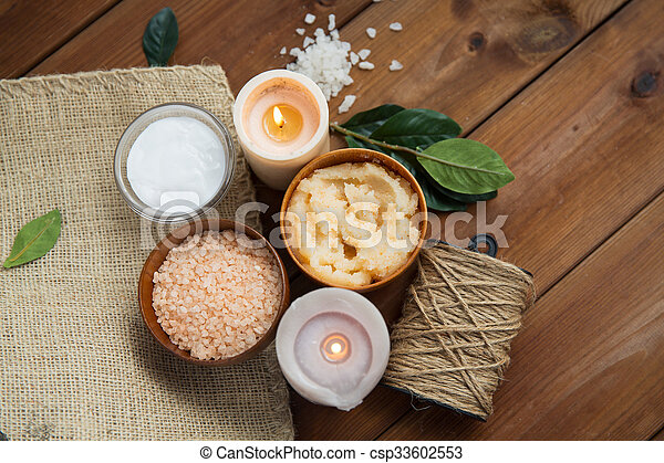 close up of natural body scrub and candles on wood - csp33602553