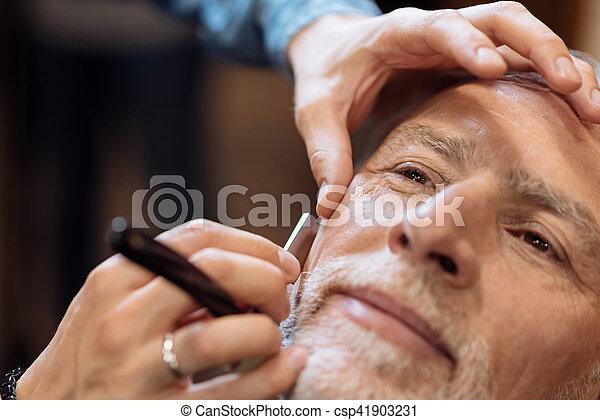 Close up of nice senior man being shaved at barbershop - csp41903231