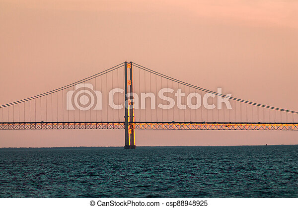 Close up of one of the towers of the Mackinac suspension bridge at sunset - csp88948925