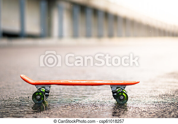 Close up of Orange Skateboard on the Wet Road in the Rain - csp61018257