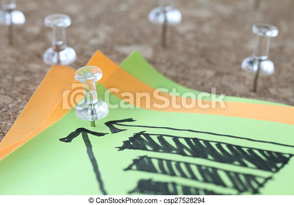 close up of pin and hand drawn business strategy graph chart on sticky note with cork board as concept - csp27528294