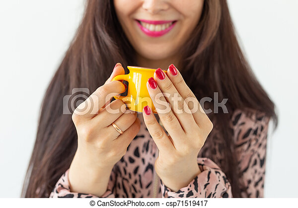 Close-up of playful young brunette woman holding in her hands a small yellow mug posing on a white background. Concept of morning coffee. - csp71519417