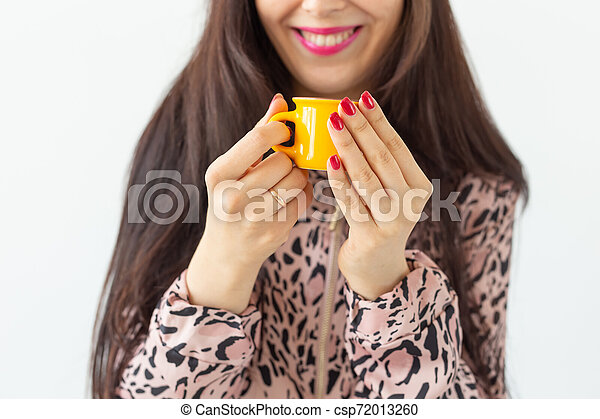 Close-up of playful young brunette woman holding in her hands a small yellow mug posing on a white background. Concept of morning coffee. - csp72013260