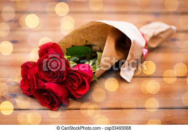 close up of red roses bunch wrapped into paper - csp33493068