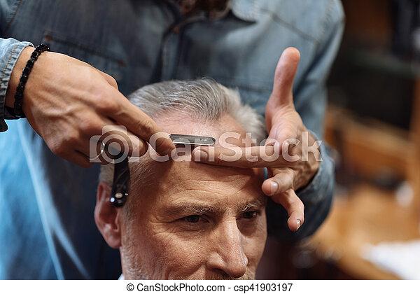 Close-up of senior man having haircut at barbershop - csp41903197