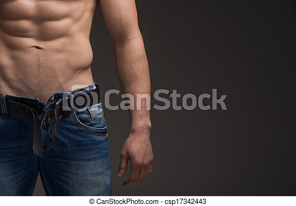 Close up of Sexy muscular man in jeans and nude torso. Standing over grey background with copy space to the right side  - csp17342443