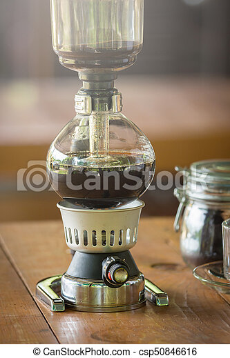 close up of siphon vacuum, coffee cup and siphon vacuum coffee maker at shop - csp50846616