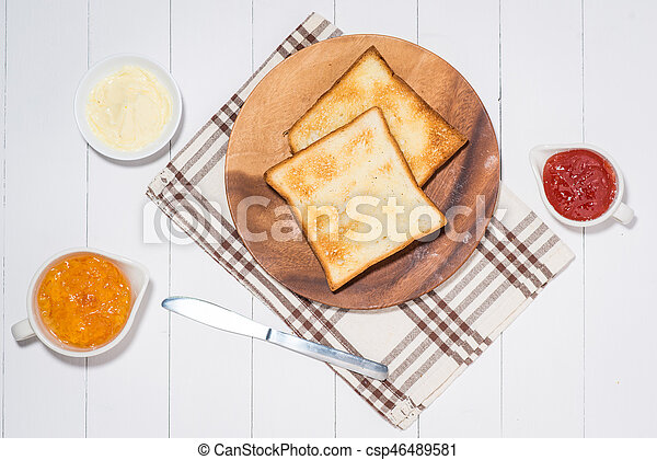 close up of slice of toast bread with jam and butter on wood table