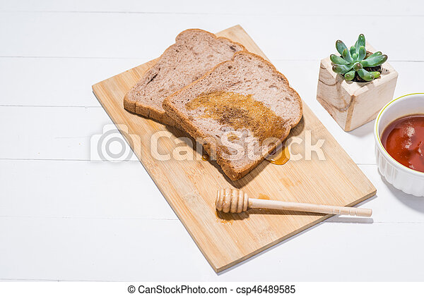 close up of slice of toast bread with honey on wood table