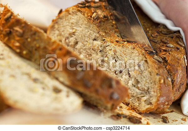 Close up of Slicing Rustic Wholemeal Seeded Loaf of Bread - csp3224714