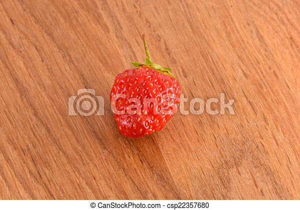 close up of small strawberry on wood - csp22357680