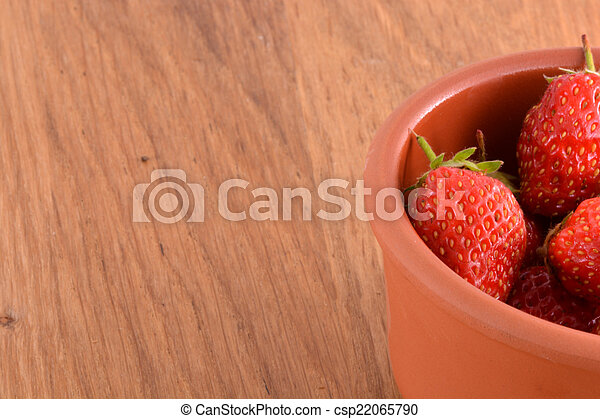 close up of small strawberry on wood - csp22065790