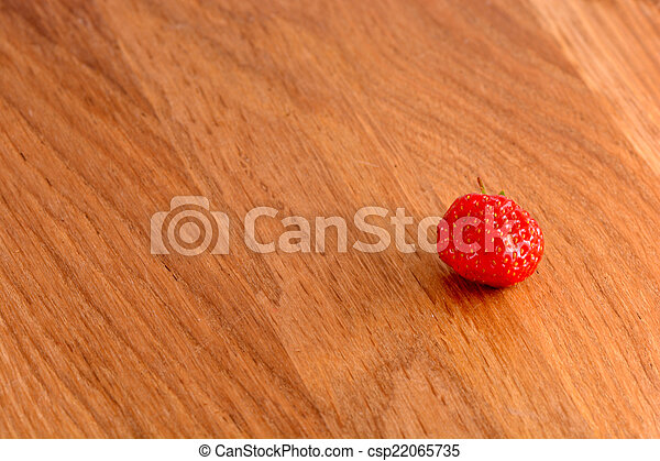 close up of small strawberry on wood - csp22065735