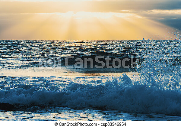 Close up of small waves under a shining sun at sunset - csp83346954
