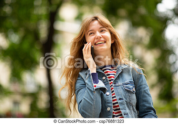 Close up of smiling young woman talking with mobile phone in park - csp76881323