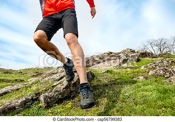 Close-up of Sportsman's Legs Running on Rocky Mountain Trail. Active Lifestyle and Adventure Concept - csp56799383