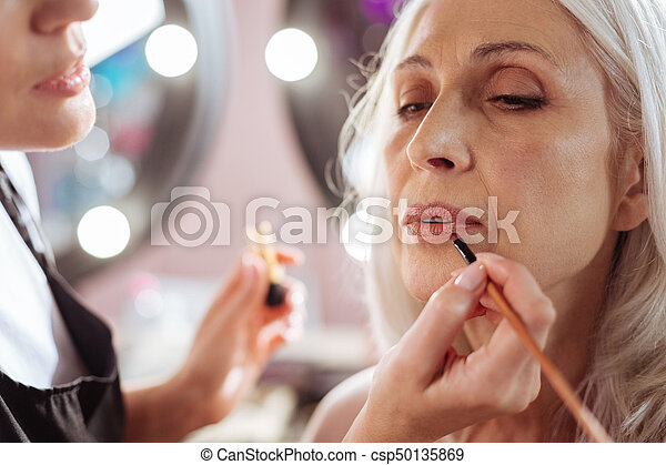 Close up of stylists hands applying lipstick to clients lips - csp50135869