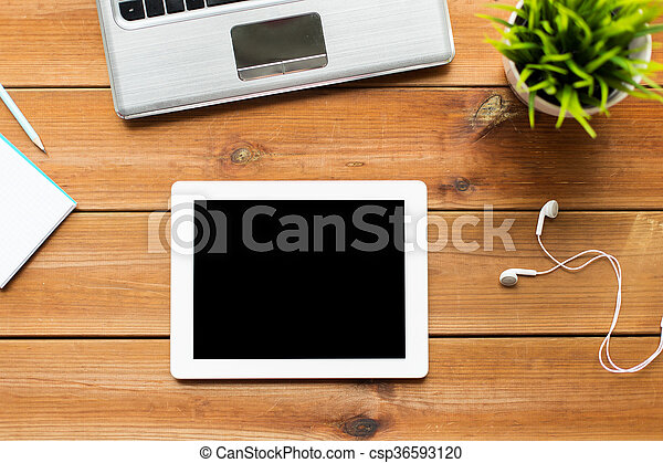 close up of tablet pc computer on wooden table - csp36593120