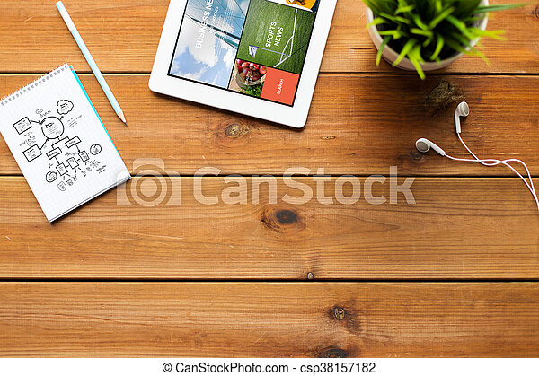 close up of tablet pc with news on wooden table - csp38157182