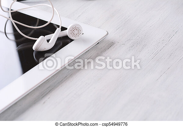 Close up of tablet with earphones on wooden table - csp54949776