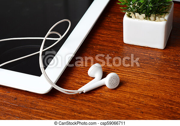 Close up of tablet with earphones on wooden table - csp59066711