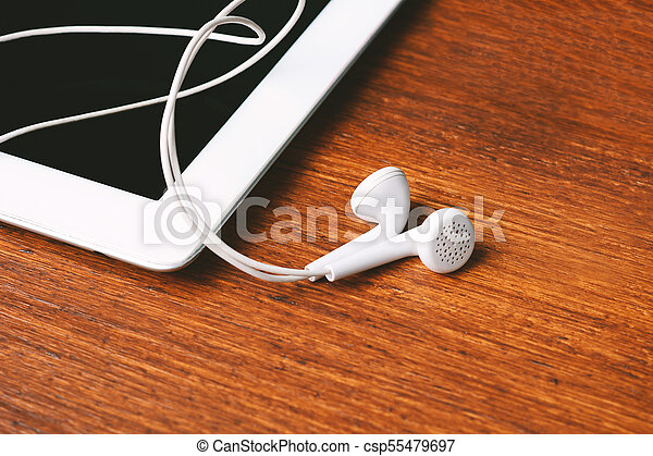 Close up of tablet with earphones on wooden table - csp55479697