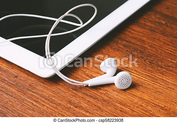 Close up of tablet with earphones on wooden table - csp58223938