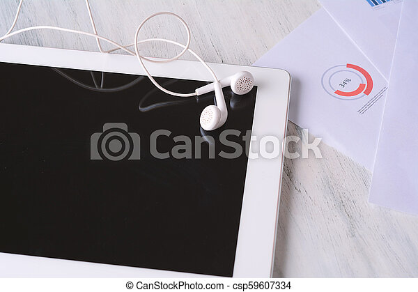 Close up of tablet with earphones - csp59607334