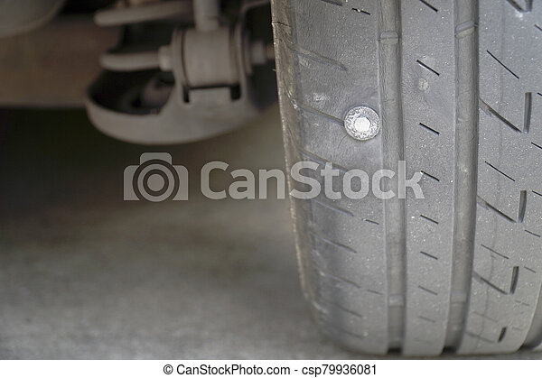 Close-up of the tire where the screw is stuck, causing the tire to leak, The most problems that cause flat tires. - csp79936081
