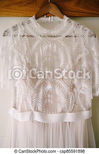 Close-up of the top of a bride's dress on a wooden hanger. - csp85591898