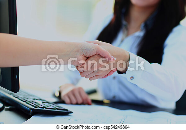 Close Up Of Two Women Shaking Hands, Indoors. - csp54243864