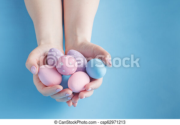 Close up of woman holding colorful Easter eggs - csp62971213