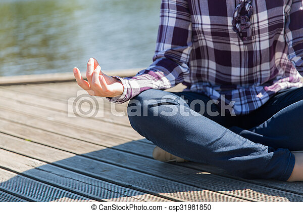 close up of woman in yoga lotus pose outdoors yoga