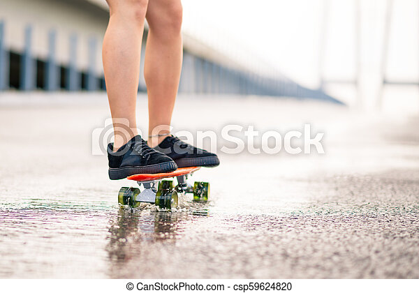 Close up of Woman Legs Riding Orange Skateboard on the Wet Road in the Rain - csp59624820