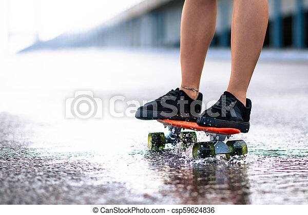 Close up of Woman Legs Riding Orange Skateboard on the Wet Road in the Rain - csp59624836