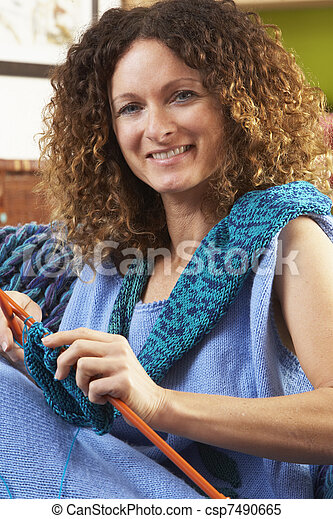 Close Up Of Woman Sitting In Chair Knitting - csp7490665