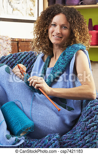 Close Up Of Woman Sitting In Chair Knitting - csp7421183