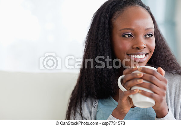 Close up of woman with a cup on sofa - csp7731573