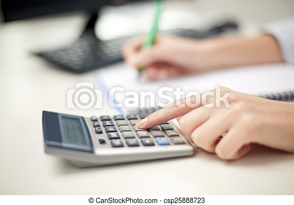 close up of woman with calculator taking notes - csp25888723