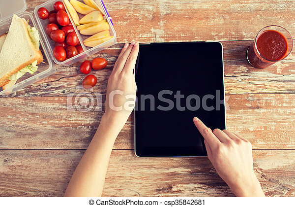 close up of woman with tablet pc food on table - csp35842681
