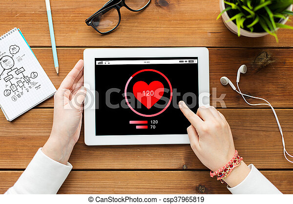 close up of woman with tablet pc on wooden table - csp37965819