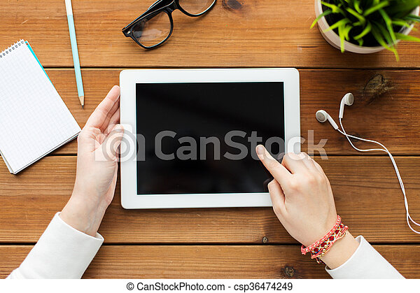 close up of woman with tablet pc on wooden table - csp36474249
