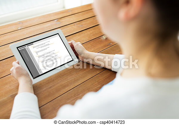 close up of woman with tablet pc on wooden table - csp40414723