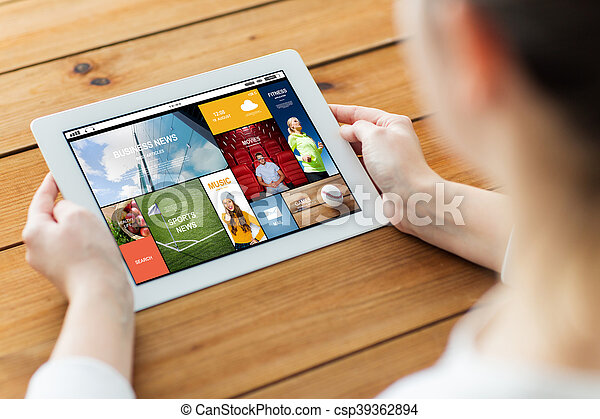 close up of woman with tablet pc on wooden table - csp39362894