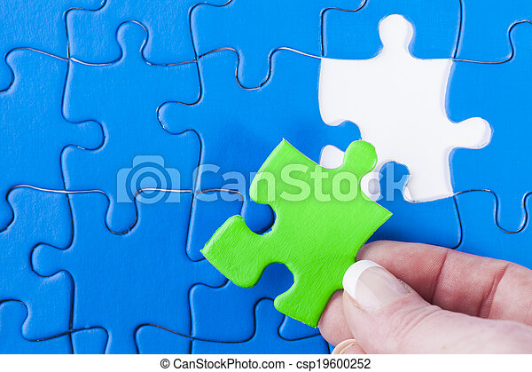 Close up of woman's hand placing missing piece in Jigsaw puzzle  signifying problem solving and decision making - csp19600252