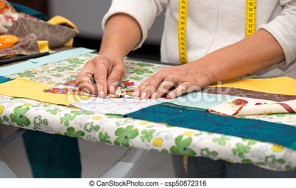Close up of woman's hand sewing patchwork - csp50872316